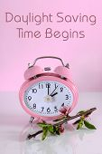 picture of daylight-saving  - Daylight savings time begins clock concept for start at Spring against a pink background with text message - JPG