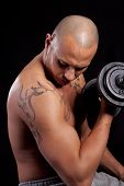 foto of bald man  - Young bald strong man is working out over black background - JPG