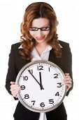 Young business woman holding big clock in hands.