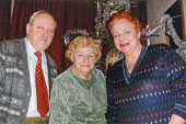 Vintage photo of elderly woman with her son and daughter in law in front of Christmas tree, nineties