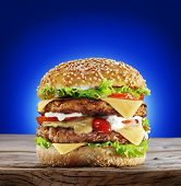 Hamburger on old wooden table. Blue background.