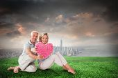 Happy couple sitting and holding heart pillow against stormy sky over city