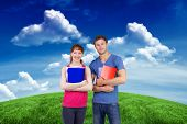 Two students both with notepads against green field under blue sky