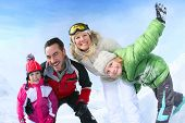 stock photo of family ski vacation  - Cheerful family of 4 enjoying winter vacation - JPG