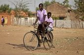 TORIT, SOUTH SUDAN-FEBRUARY 20, 2013: Unidentified schoolboys ride their bike from school in South Sudan