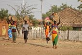 TORIT, SOUTH SUDAN-FEBRUARY 20, 2013: Unidentified women carry heavy loads on their heads in South Sudan