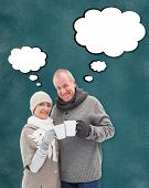 Happy mature couple in winter clothes holding mugs against teal