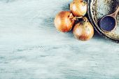 foto of spooning  - Old kitchen pan wooden spoon three onions on wooden table - JPG