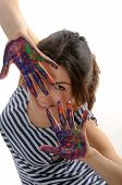 Woman In Striped T-shirt Looks Out Palms Painted In Colorful Paint
