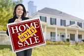 Smiling Hispanic Woman Holding Sold Home For Sale Sign In Front of Beautiful House.