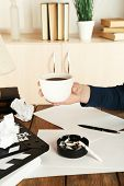 Female hand with cup of coffee at desktop with moving clapper and working mess on light cupboard background