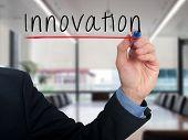 Businessman hand writing innovation in the air - Stock image