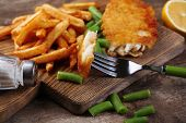 Breaded fried fish fillet and potatoes with asparagus on cutting board and wooden planks background