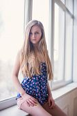 Beautiful longhaired blonde young woman sitting on the windowsill. Cozy morning, lifestyle photograp