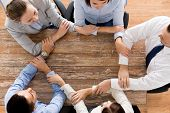business, people, cooperation and team work concept - close up of creative team sitting at table and holding hands in office
