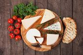 image of cheese platter  - Assorted cheese on wooden platter - JPG