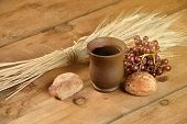 Communion elements with wine, bread, wheat, grapes and cup on vintage table with sunlight flair effect