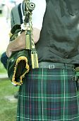 picture of bagpiper  - Piper wearing a kilt and holding green bagpipes - JPG