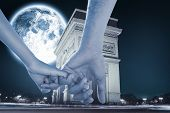 Loving young couple holding hands against large moon over arc de triomph