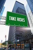 The word take risks and green billboard sign against skyscraper in city