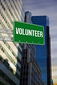 The word volunteer and green billboard sign against low angle view of skyscrapers