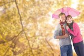 Couple standing underneath an umbrella against tranquil autumn scene in forest