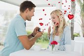stock photo of marriage proposal  - Man proposing marriage to his shocked blonde girlfriend against red heart balloons floating - JPG