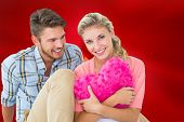 Composite image of attractive young couple sitting holding heart cushion