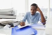 Tired businessman writing notes at desk in the office