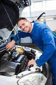 stock photo of hoods  - Mechanic examining under hood of car at the repair garage - JPG