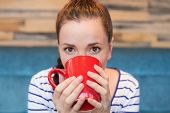 Young woman having mug of coffee at the cafe