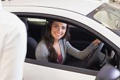 Happy female driver at the wheel sitting in her car at new car showroom