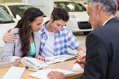 Smiling couple reading a booklet at new car showroom