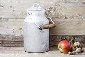 An apple, walnuts and  an aluminum old milk can on a wooden background