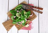 Mix salad leaves with sliced cucumber and onion on cutting board and color wooden planks background