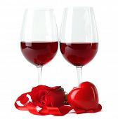 Composition with red wine in glasses, red rose, ribbon and decorative hearts isolated on white