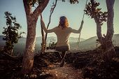 Young Woman On Swing In The Mountaind