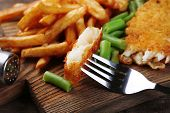 Breaded fried fish fillet and potatoes with asparagus on wooden cutting board background