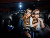Affectionate mother and daughter watching 3D movie in cinema theater