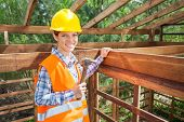 Portrait of confident female construction worker holding hammer in timber frame at site