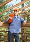 Thoughtful male construction worker carrying rolled pipe in incomplete wooden cabin at site