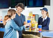 Happy expectant couple buying snacks from female seller at cinema concession stand