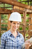 Portrait of beautiful architect holding blueprint in wooden cabin at construction site