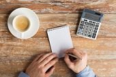 business, education, people and technology concept - close up of male hands with calculator and coffee cup writing to notebook by pen on table