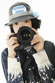 Closeup of a pretty young teen photographer with her camera held at the ready.  On a white background.