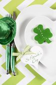 picture of leprechaun hat  - Happy St Patricks Day table place setting with heart shape plates shamrock cookie and leprechaun hat on green and white chevron stripe table vertical - JPG