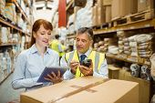 Warehouse managers looking at tablet pc in a large warehouse