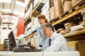 picture of warehouse  - Warehouse managers working together on laptop in a large warehouse - JPG