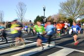 City marathon with runners in motion blur