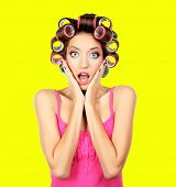 Beautiful girl in hair curlers on yellow background
